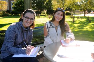 Students studying outside on a warm summer day at Adelphi's campus