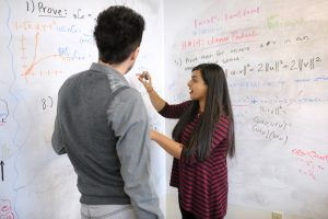 Female Adelphi student working on a mathematical equations with her professor