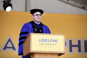 Adelphi University official addressing audience at the podium.
