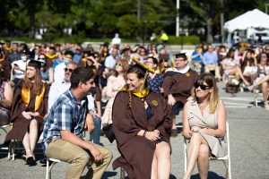 An Adelphi graduate seated with their family members. For social distancing all graduates were seated with two guests in groups of three.