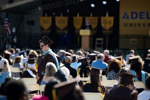 Graduate walking through seated audience with a view of the commencement stage in the background.