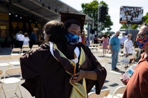 Two graduating students embrace while wearing masks.