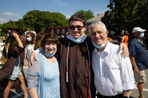 Graduate poses with parents for picture.