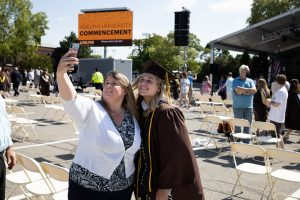 Graduate poses for picture with mother for a selfie at in-person commencement.