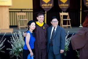Graduating student poses with parents in front of commencement stage.