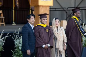 Graduating student poses with proud parents in front of commencement stage.