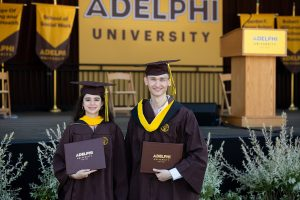 Two Adelphi graduates holding diplomas pose for a picture.