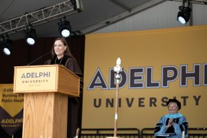 President Riordan standing behind a podium in a commencement robe, an Adelphi banner behind her.