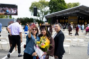 Graduate holding bouquet poses for picture with parents.