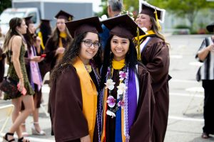 Two graduates pose for a picture.