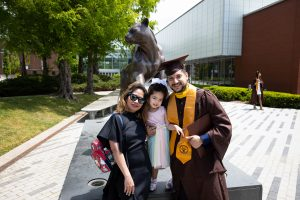 A graduate poses with his family in front of the Panther Statue on campus.