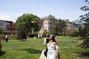 An Adelphi graduate throws her cap in front of Levermore Hall on campus.