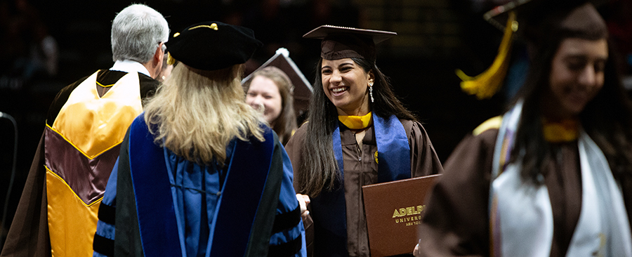 A graduate wearing a cap and gown during an Adelphi commencement ceremony.