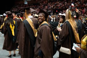 photo of a graduate wearing brown cap and gown