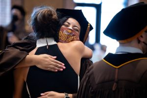 """An Adelphi doctoral candidate hugs their loved one wearing a """"Class of 2021"""" mask"""