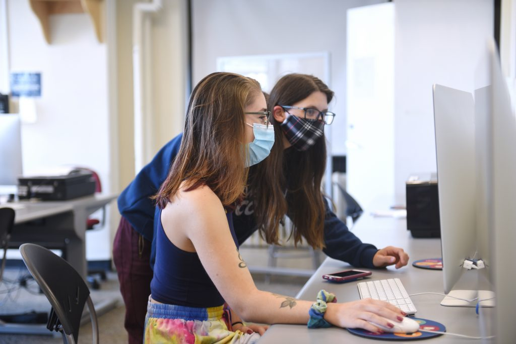 Two students masked in the computer lab