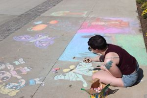 Adelphi student draws butterflies on the sidewalk during Fall Arts Festival.