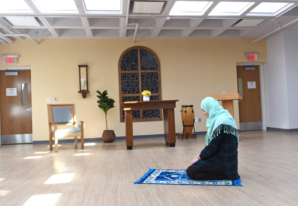 Interfaith Chapel space being used for daily prayers. Showing a muslim student facing mecca.