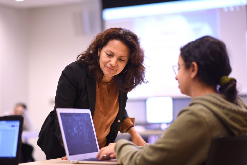Adelphi professor Ines Archer in class with a student looking at a laptop screen.