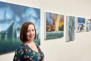 Kellyann Monaghan poses near her paintings
