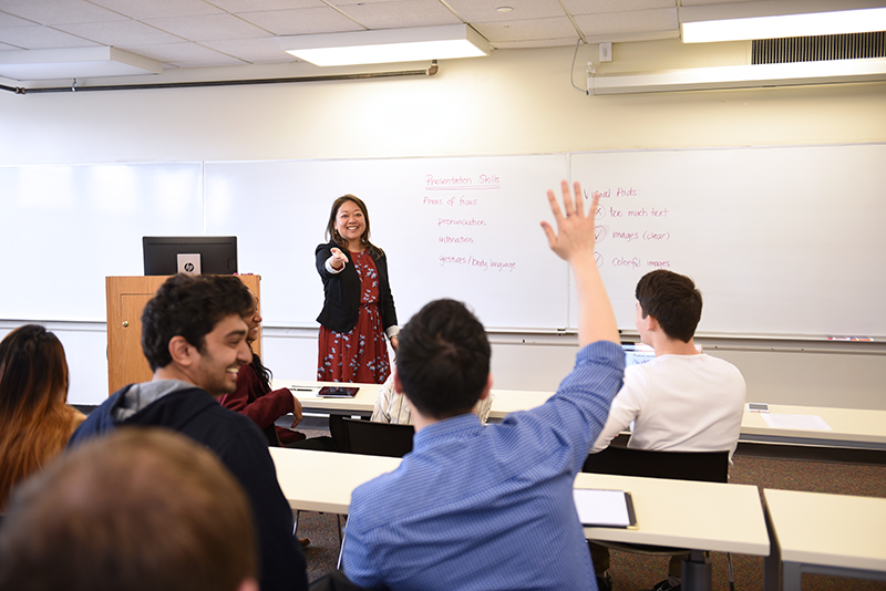 Student raises hand in classroom at Adelphi.