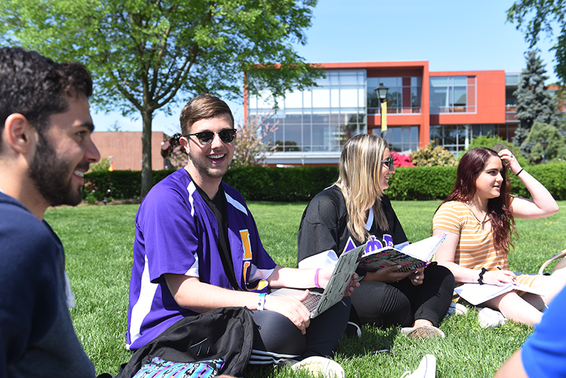 Adelphi students sitting and studying on the lawn in front of Nexus