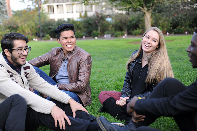 Adelphi students sitting and socializing on grass