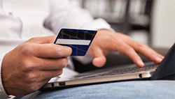 Man with credit card at a laptop