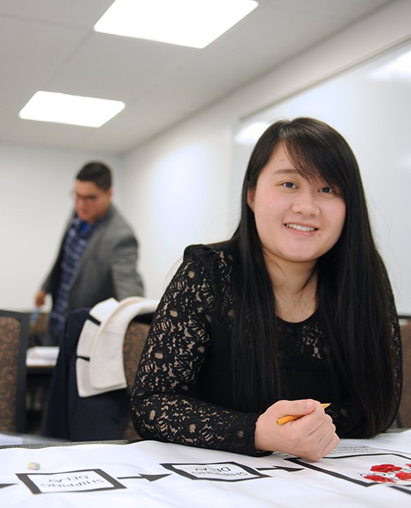 Adelphi business student in class looks at camera.