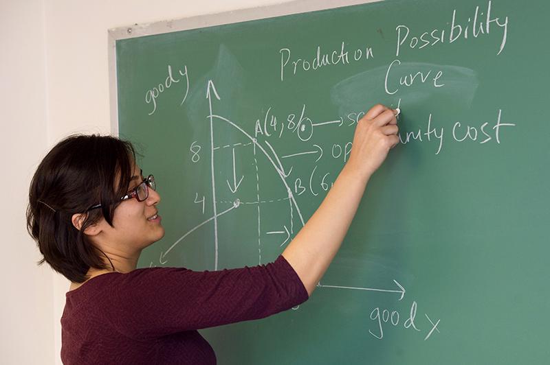 Adelphi economics student working at blackboard.
