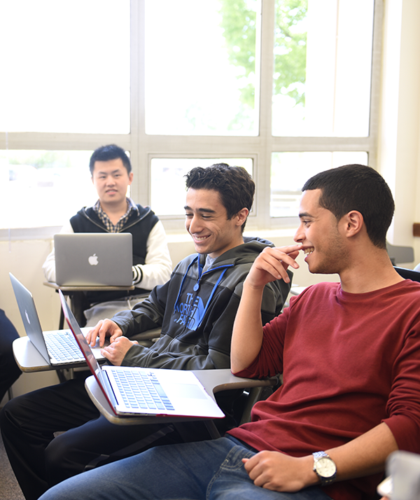Male students laugh during class.
