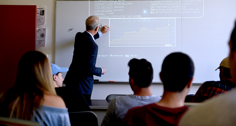 Adelphi business professor writes on whiteboard with projected chart.