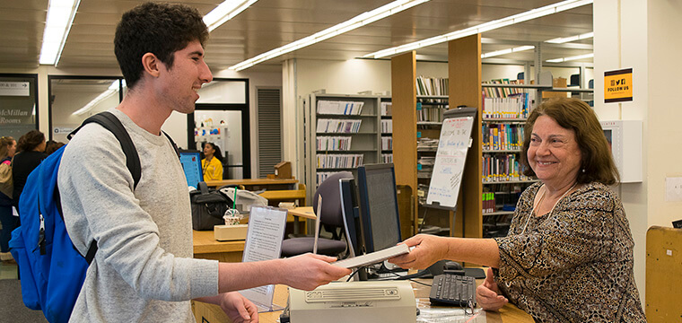 Adelphi University Libraries student borrows a book