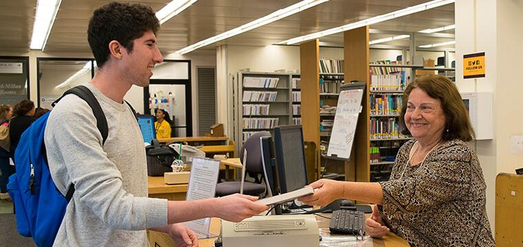 Adelphi University Libraries student borrows a book