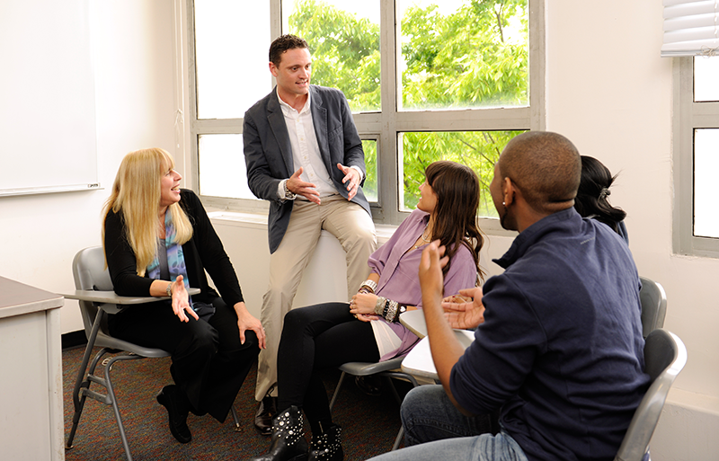 Professor passionately talking with students at Adelphi