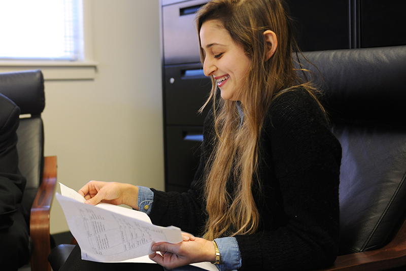 Adelphi psychology student smiling while looking at papers