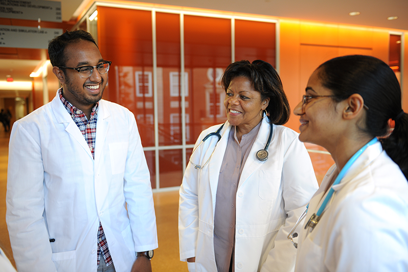 Adelphi nursing students in lab coats talking in the Nexus facility