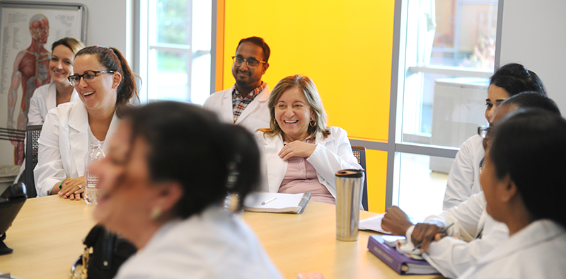 students in white lab coat laughing in a classroom