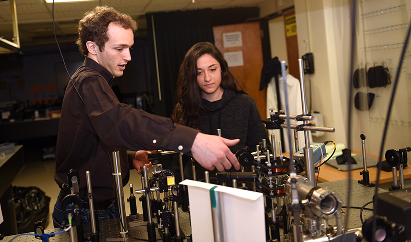 Adelphi physics students adjusting equipment in the lab