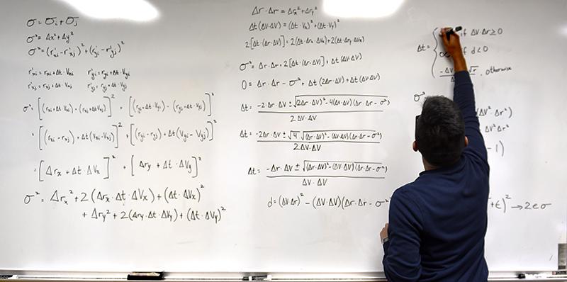 Adelphi physics student writes equation on whiteboard