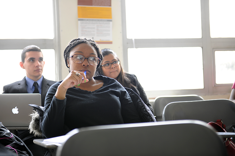 Adelphi students in backlight classroom focusing on the lecture
