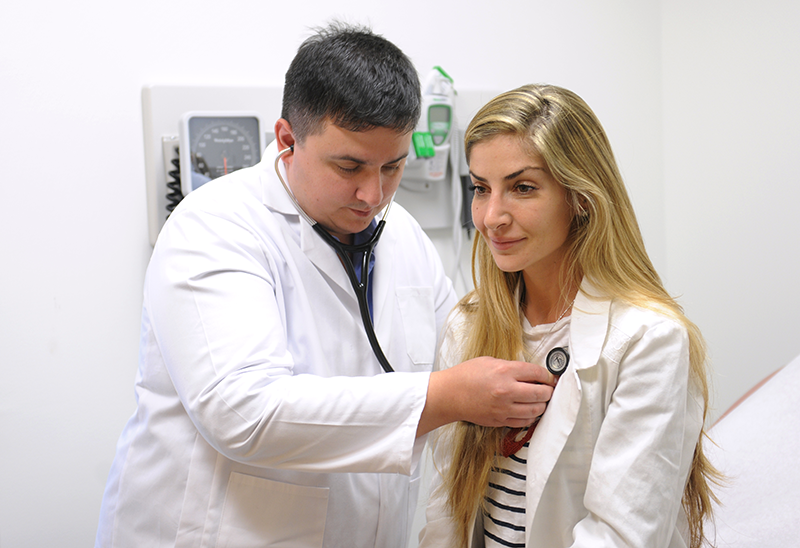 Adelphi student in white lab coat examines patient