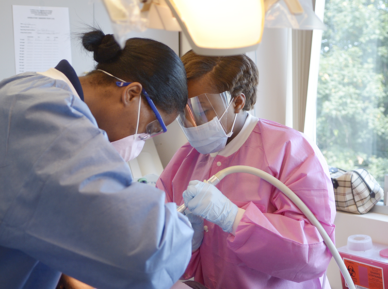 Adelphi student assists with dentristry procedure during internship
