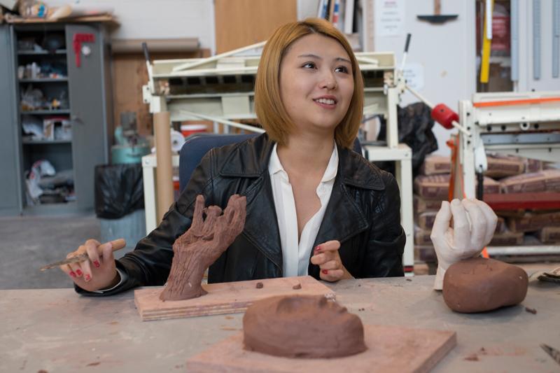 Adelphi art student in the ceramic studio