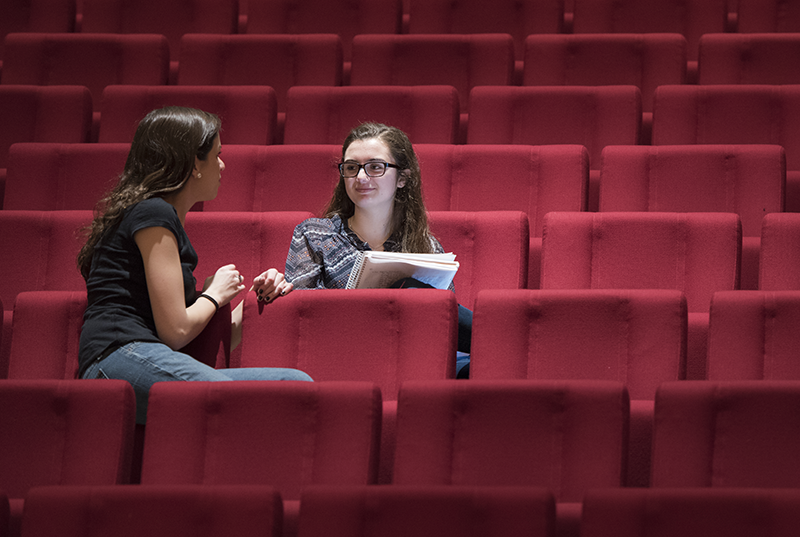 Two acting students a Adelphi University talk in red audience seats.