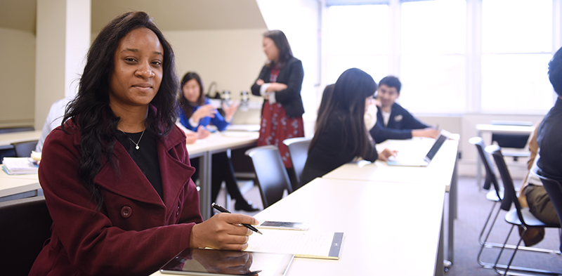 Adelphi student smiles at camera during class