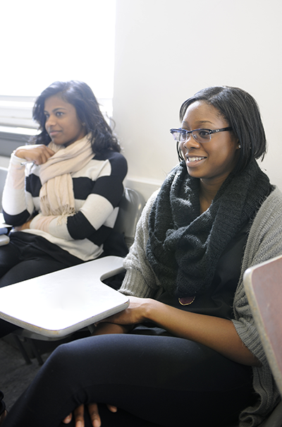 Two Adelphi students smile during class
