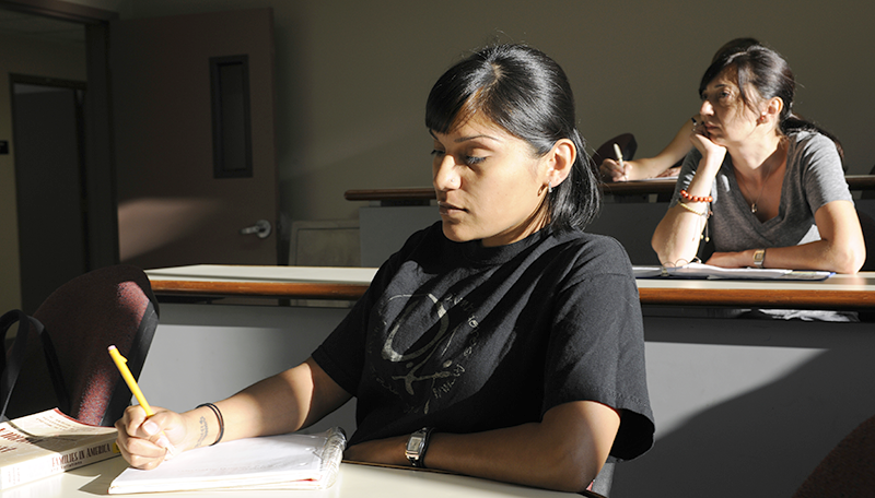 Adelphi female student takes notes during lecture