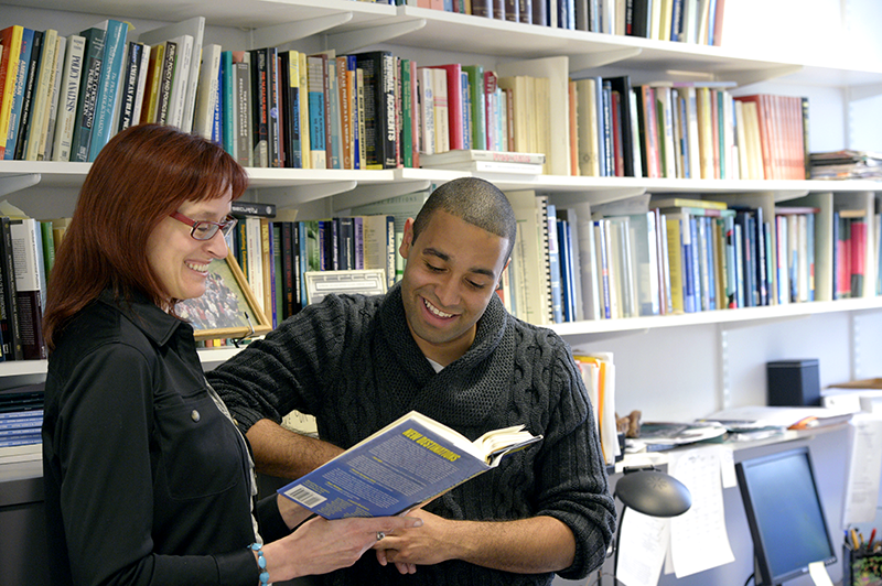 Maggie Gray in her office with a student looking at a book