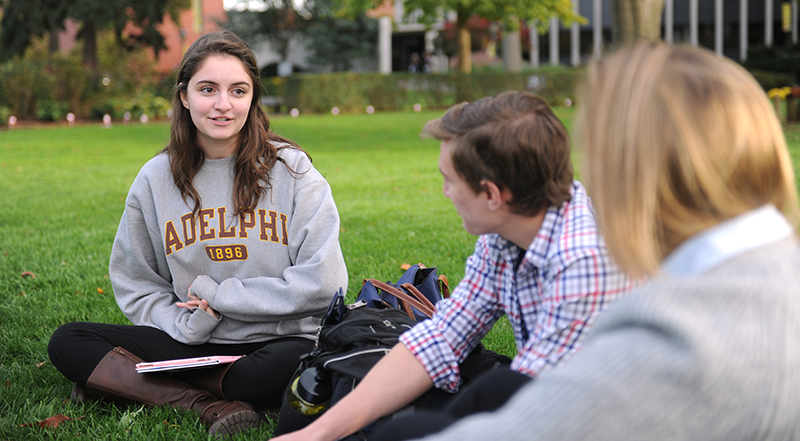 Adelphi student talking with others on the lawn